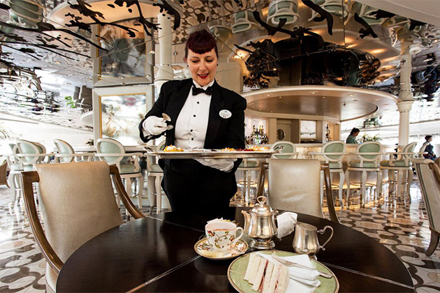 Female crew member serving canapes at the Afternoon Tea in the Palm Court on Crystal Symphony