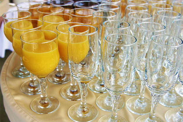 Mimosas and empty glasses on a buffet table