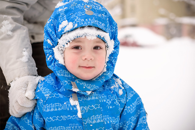 Happy little smiling boy outdoors in the snow in winter clothing. Kid has a snow on his face.
