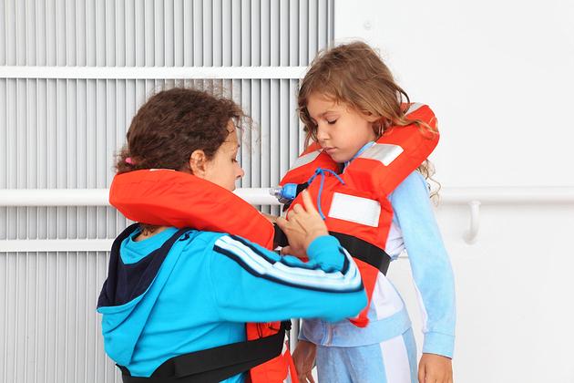 Mother dresses her daughter in orange life jacket