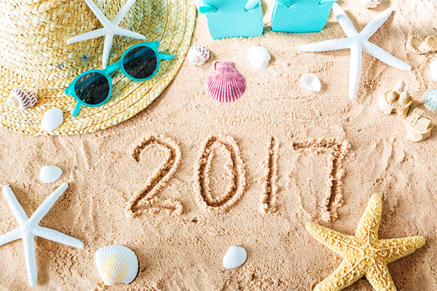 2017 written in the sand surronded by shells, starfish and travel items