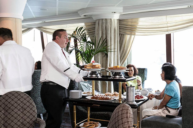 Butler serving Afternoon Tea guests canapes and pastries from a rolling cart