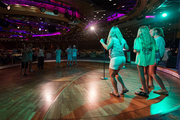Group of girls singing karaoke in a dimly-lit lounge on Enchantment of the Seas