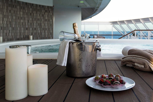 Bottle of Champagne, candles and chocolate-covered strawberries beside a hot tub