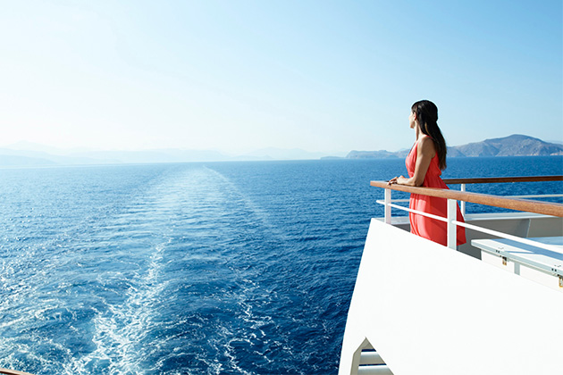 Woman overlooking wake from a Seabourn ship deck