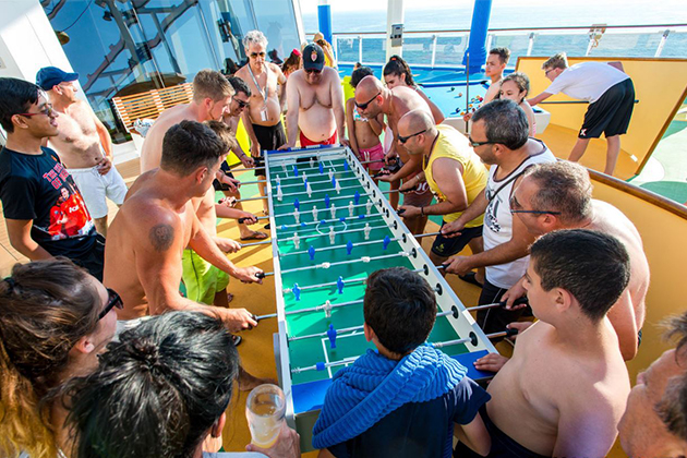 Group of multi-generational passengers playing foosball at SkyGreens on Carnival Vista