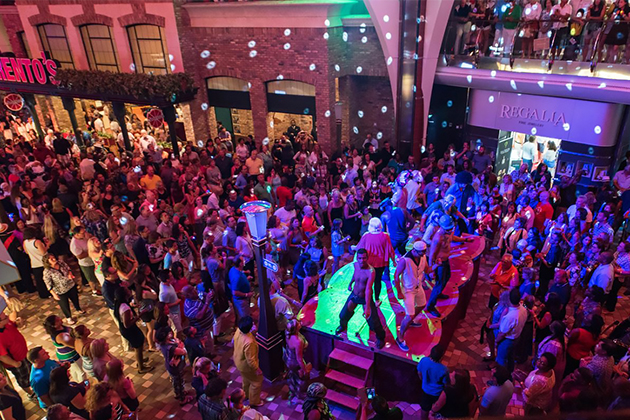 Large group of people dancing in the low-lit Royal Promenade on Oasis of the Seas