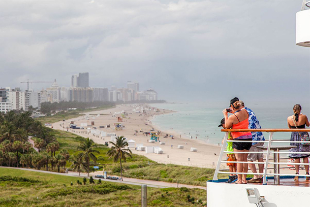 Passengers take photographs of a beach at Sailaway, while Carnival Sensation cruises out of Miami