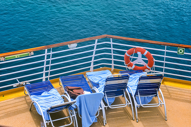 Lounge chairs on deck of cruise ship with towels on them in sunny caribbean