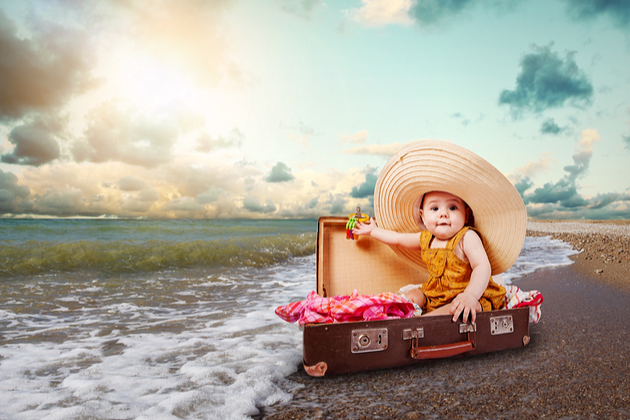 Funny baby girl traveler sitting in retro suitcase