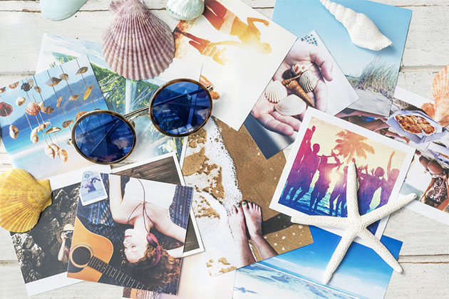 Pile of vacation photos with shells and sunglasses on top