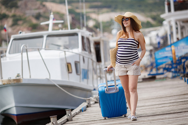Young pregnant woman with luggage at the docks