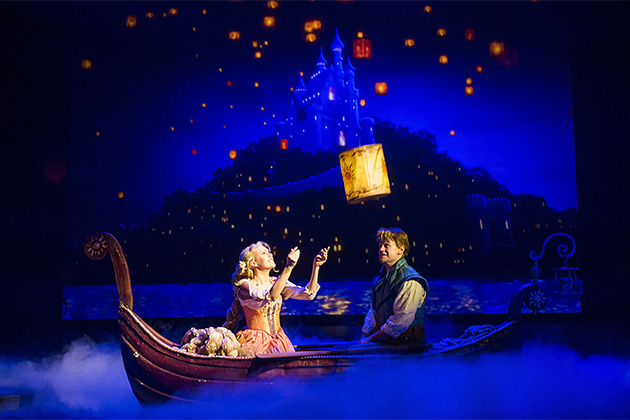 Characters from Tangled musical releasing a lantern from a small paddle boat