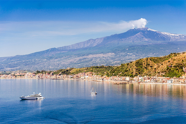 sicilian coastal landscape with cruising boats view from Taormina with the mount Etna in the background