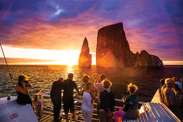 Lindblad passengers looking out towards the towering Kicker Rock at sunset, from a Lindblad expedition cruise deck