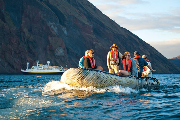 Lindblad Expeditions passengers on a zodiac heading to shore, with shot of cruise ship in the background