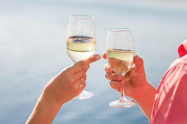 Couple toasting glasses of white wine with water in the background