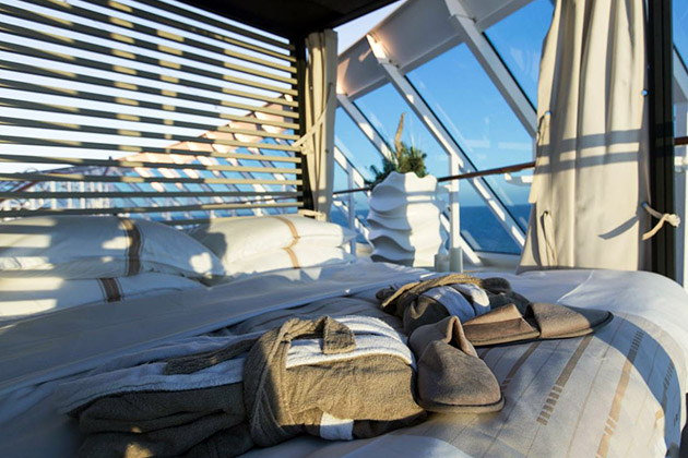 Robes and slippers on an outdoor cabana bed for the Nights in Private Places experience