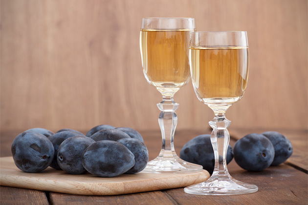 Plum brandy or schnapps surrounded by plums