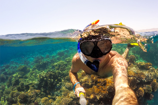 Underwater and surface split view in the tropics paradise with snorkeling man, fish and coral reef, under and above waterline, beautiful view on tropical sea