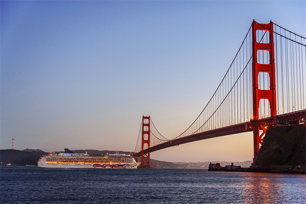 A white cruise ship passing under the Golden Gate Bridge in San Francisco at dusk.