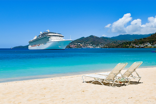 Cruise ship in Caribbean Sea with beach chairs on white sandy beach. Summer travel concept.