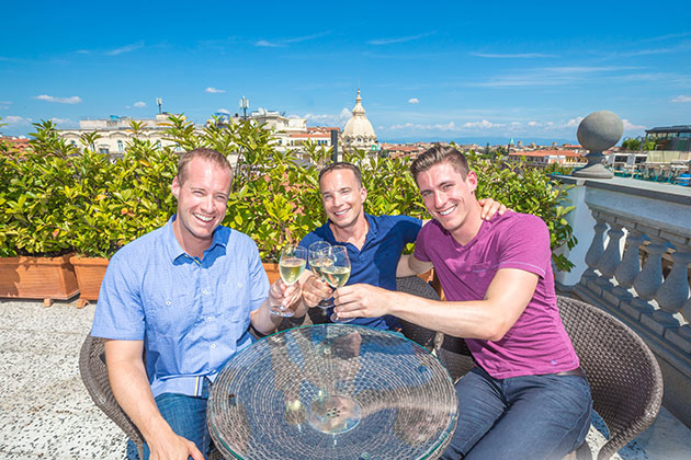 Three men drinking wine on a balcony