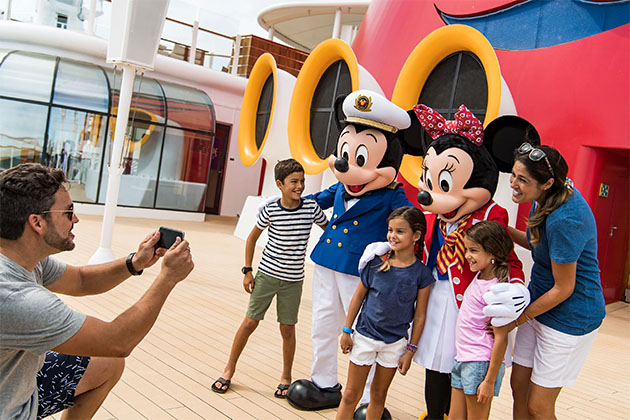 Mickey and Minnie greeting a family on a Disney cruise