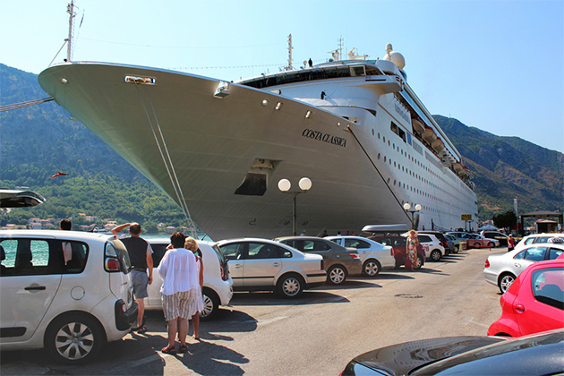 people walk on the pier to which moored cruise ship in a port surrounded by mountains. along the pier there are numerous cars