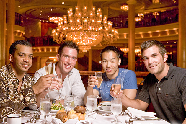 Four gay men toasting at dinner onboard a cruise ship