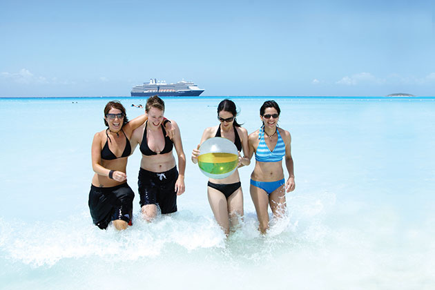 Four women on beach with cruise ship in background