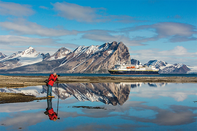 Shot of a National Geographic Explorer passenger photographing Goose Bay in Norway with the ship in the background