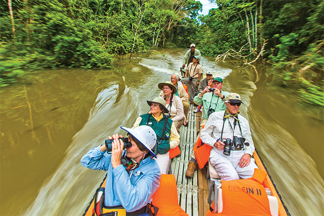 Passengers on a mid-day Skiff ride through a tropical reserve in Peru