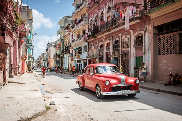 Classic red American car being used as a taxi in downtown Havana, Cuba, with locals