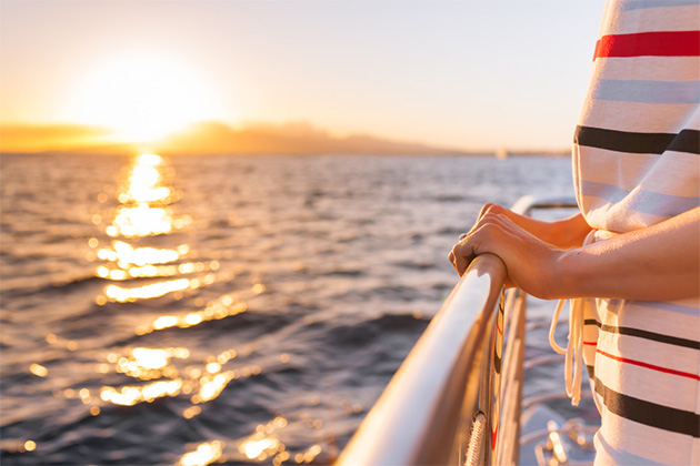 Woman holding onto a ship balcony, with sea and sunset in the background