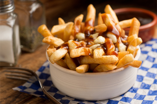 Close-up shot of Poutine in a bowl on a blue checkered tablecloth