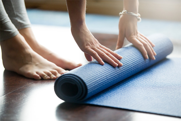 Close-up of a woman unfolding blue fitness mat