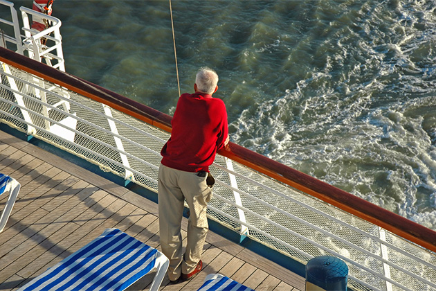 A senior man looks out over the rail of a cruise ship