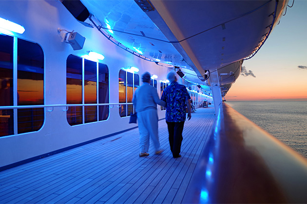 Elderly Couple Walking On Cruise Ship Deck in Evening