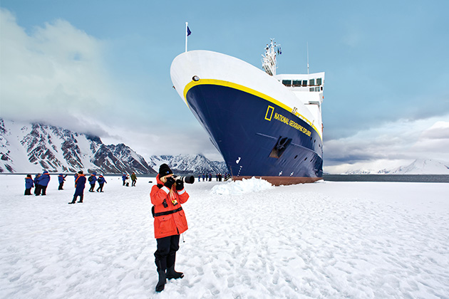 passenger photographing antarctica landscape with national geographic explorer docked in the background
