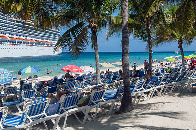 Crowded beach in Grand Turk with Carnival Valor docked in port