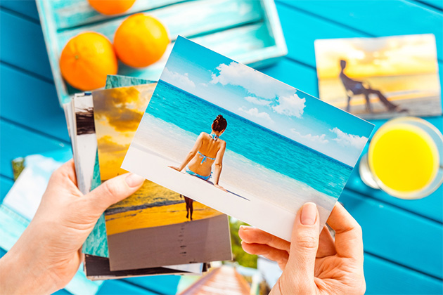 Woman looking at brightly colored travel photos in her hands