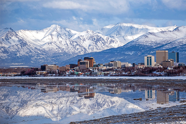 Anchorage city skyline, with reflection of towering, snowy mountains in the water below