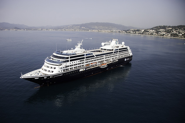 Aerial shot of Azamara Quest with Cannes shoreline in the backgroune