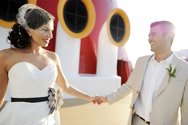 Married couple on Disney Cruise Line on their wedding day, with Disney funnel in the background