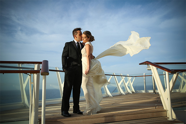 Married couple onboard a Royal Caribbean ship sun deck during sunset