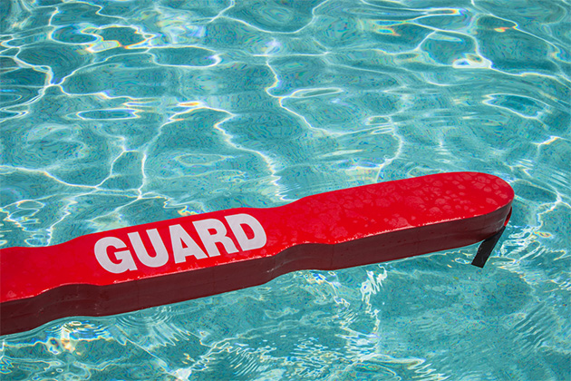 A close up shot of a life guards red rescue tube floating in a pool