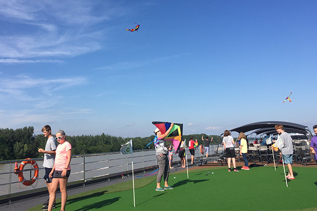 Kids and parents flying kites on the sun deck of ms Grace
