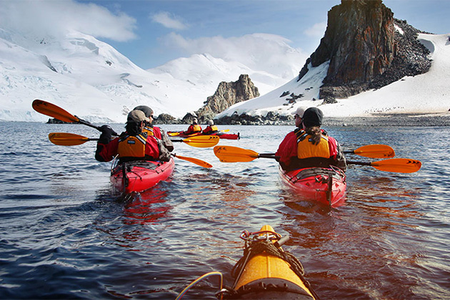 Three kayakers with Antarctic backdrop