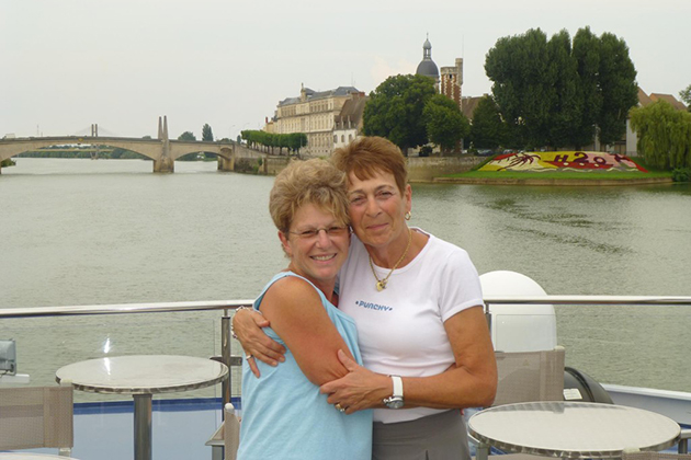 Two mature women hugging on river boat with bridge in background